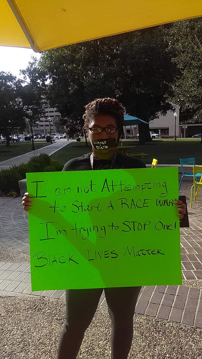 A participant in the #blacklivesmatter rally holds up a sign. Photo by La Juana Chambers.