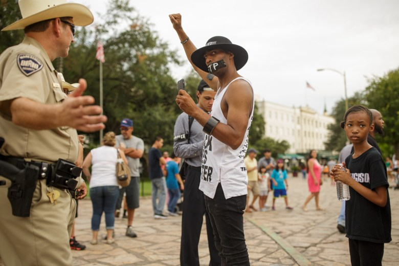 Mike Lowe holds up his fist as Alamo Rangers Security officers Garza and Kubena ask Mike and his daughter Naomi, 9, to step off of Alamo property. Photo by Scott Ball.