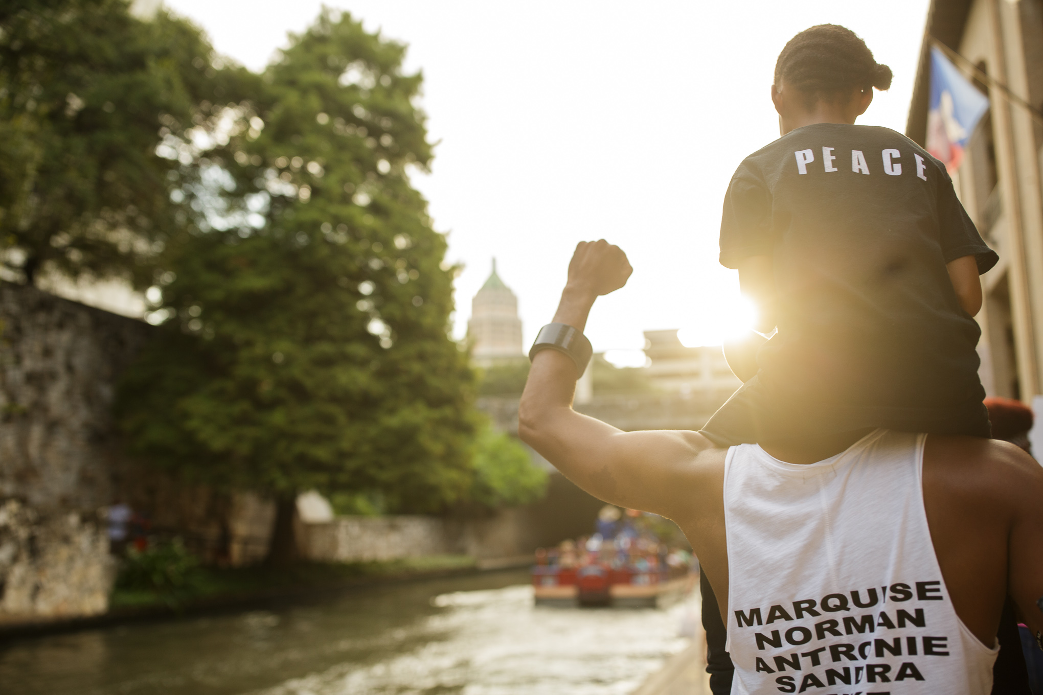 Mike Lowe raises his fist as he carries his daughter Naomi, 9, along the San Antonio River Walk. Photo by Scott Ball.