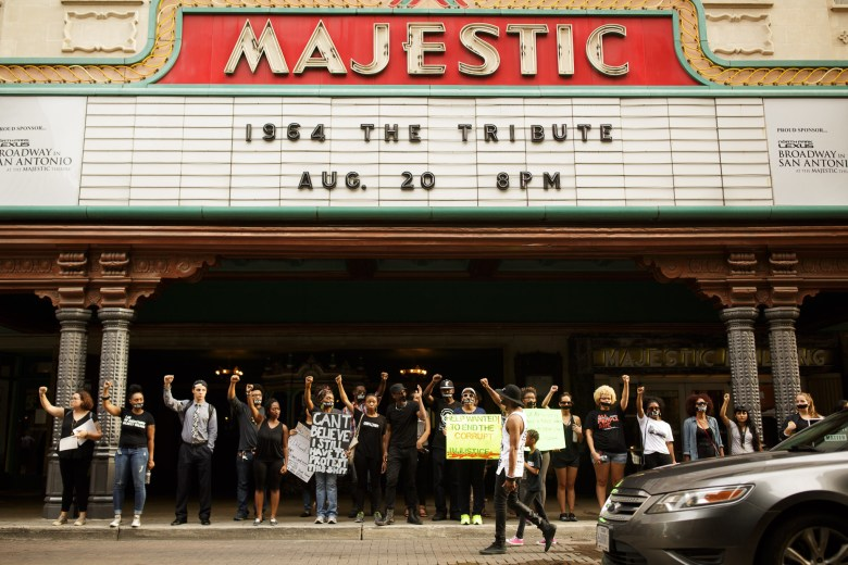 Protestors assemble underneath the Majestic Theatre as traffic passes on Houston Street. Photo by Scott Ball.