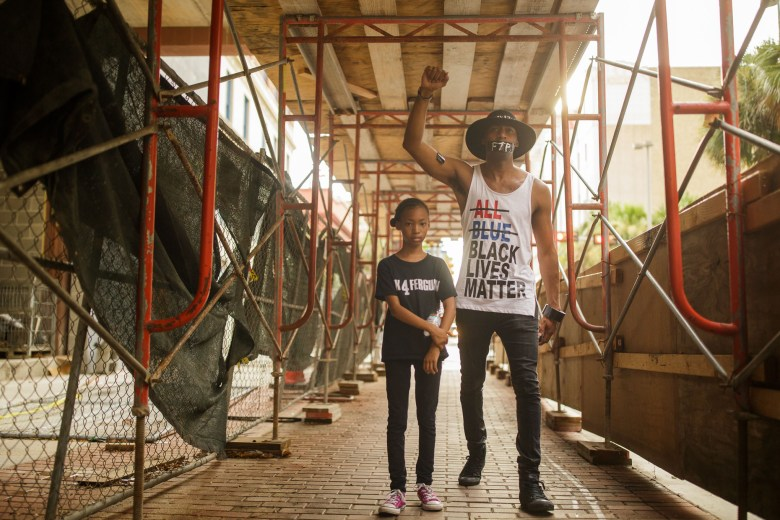 Mike Lowe and his daughter Naomi, 9, walk under scaffolding along Houston Street. Photo by Scott Ball.