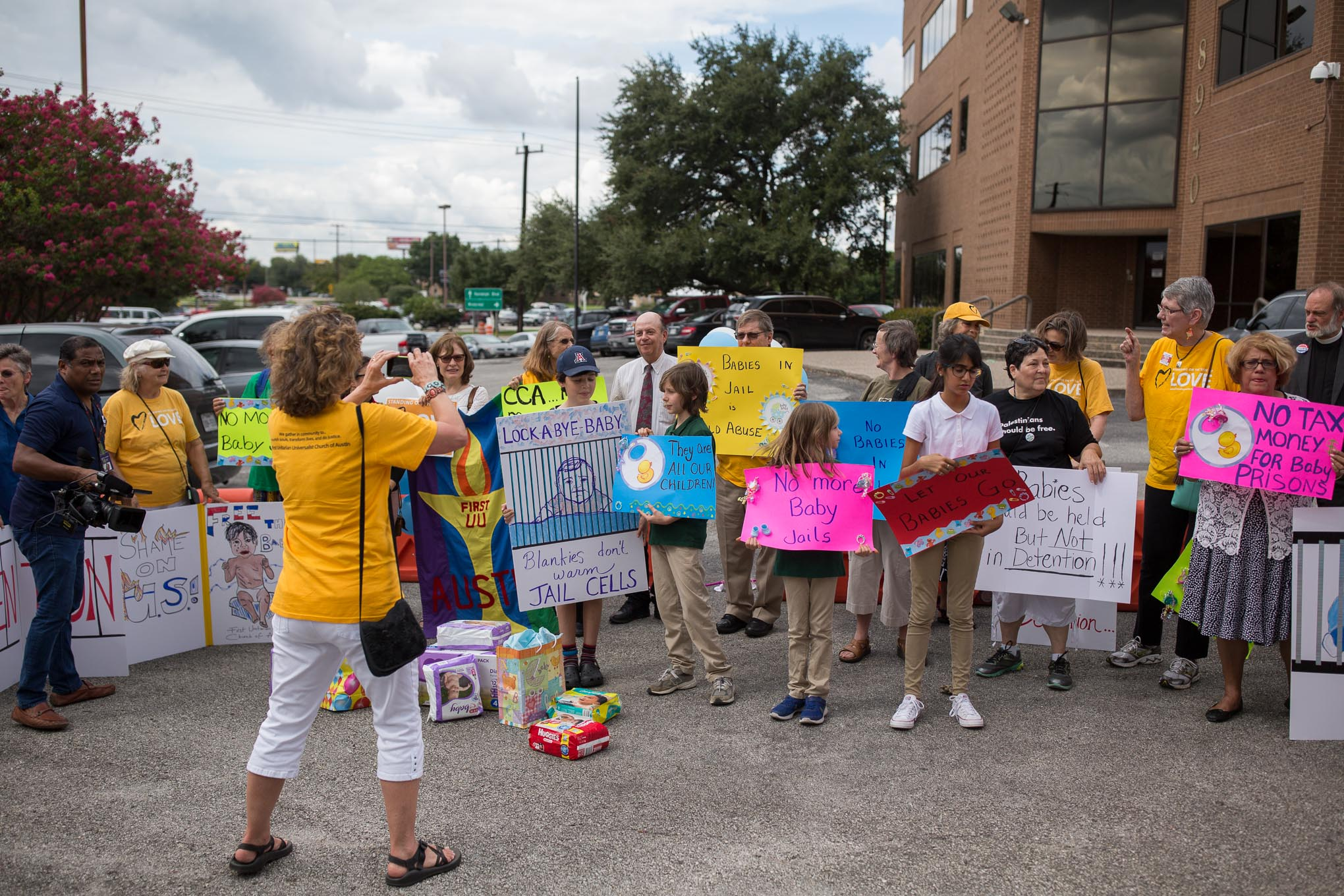 Organizers set up in the parking lot of the United States Citizenship and Immigration Services (USCIS) to protest the imprisonment of underage immigrants in detention facilities. Photo by Scott Ball.