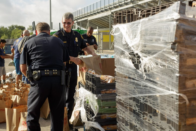 San Antonio Police Chief William McManus socializes with Capt. Troy Torres as he loads bags of food for the San Antonio Food Bank. Photo by Scott Ball.
