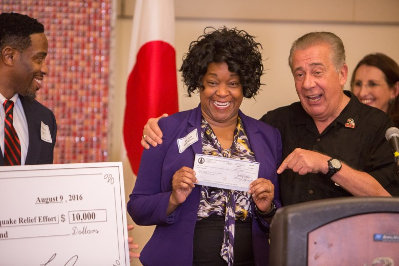 CPS Energy President Paula Gold-Williams holds up a check donated by The University of Incarnate Word as she is held by UIW President Louis Agnese. Photo by Scott Ball.