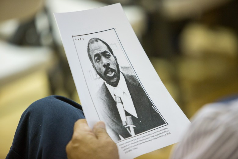 An attendee holds up a photograph of Reverend Raymond Callies. Photo by Scott Ball.