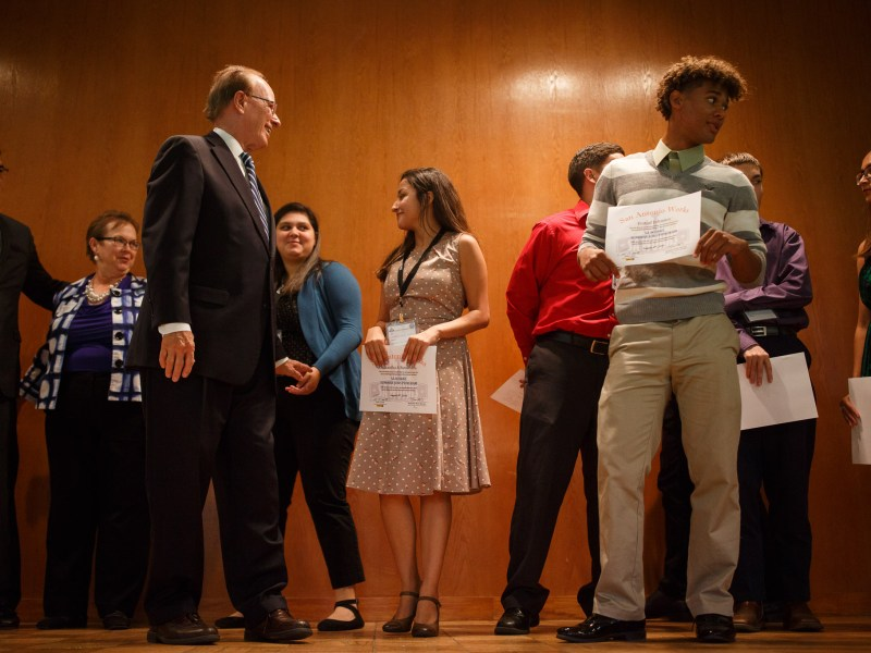 Bexar County Judge Nelson Wolff stands on stage as he congratulates Bexar County summer interns on completing the program. Photo by Scott Ball.