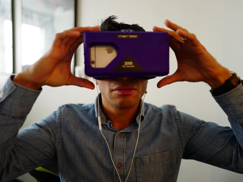 Rivard Report Marketing Director Jaime Solis tries virtual reality using a Merge VR Goggles. Photo by Scott Ball.