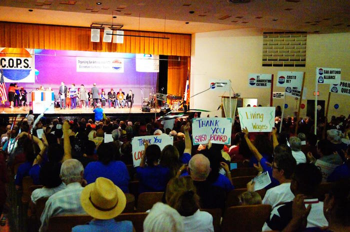 Members of the San Antonio Alliance of Teachers and Support Personnel raise signs thanking SAISD for working with COPS/Metro on raising wages for their lowest paid workers. Photo by Sean Encino.