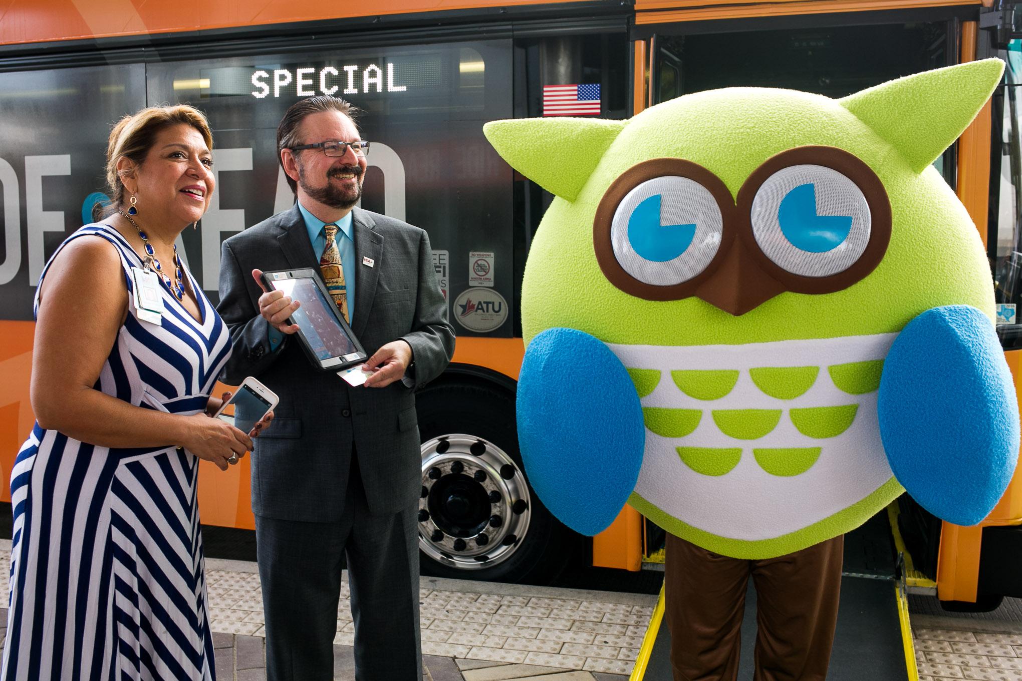 VIA Metropolitan Transit President/CEO Jeffrey C. Arndt poses with San Antonio Library mascots Tecolote. Photo by Kathryn Boyd-Batstone.