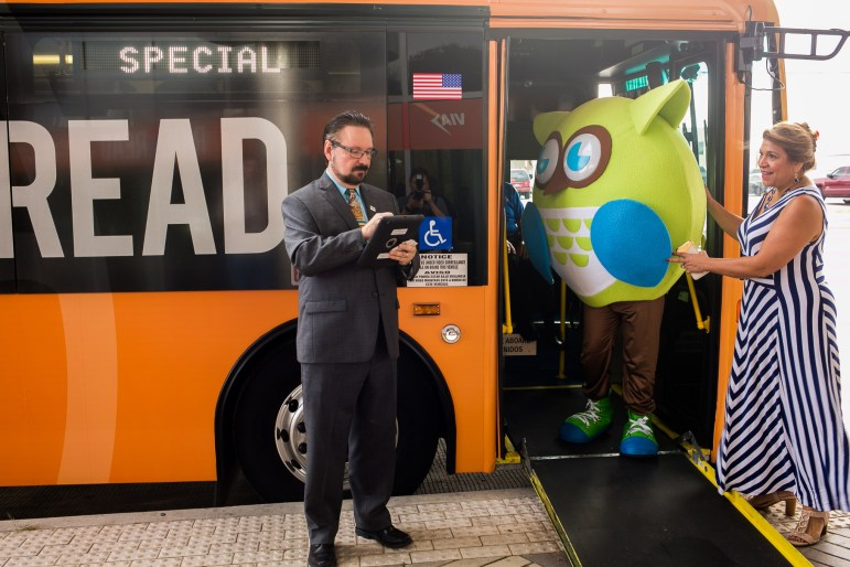 VIA Metropolitan Transit President/CEO Jeffrey C. Arndt prepares his downloaded book as San Antonio Library mascots Tecolote exists the bus.