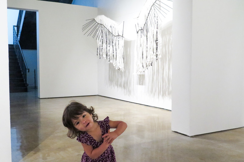 June Gonzalez stands in front of an art piece depicting eagle wings that has several embedded photo strips of the U.S.-Mexico border crossing. Photo by Rocío Guenther.