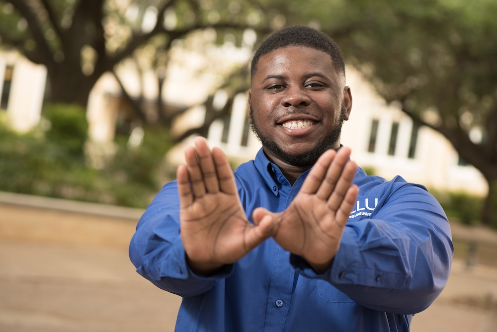 """Christopher Robinson gives a """"wings up"""" hand sign has become a favorite tradition at Our Lady of the Lake University. Photo courtesy of OLLU."""