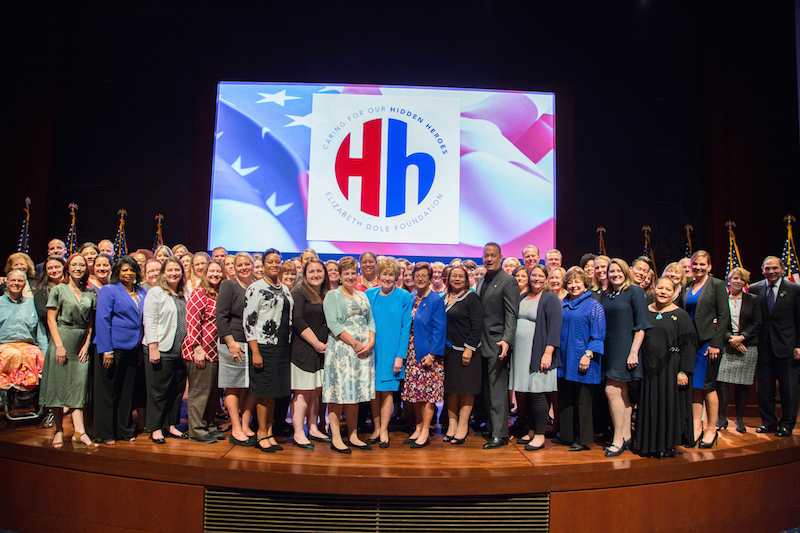 Hidden Heroes speakers and more than 60 Dole Caregiver fellows on stage with Senator Dole and Tom Hanks. Photo by Lisa Nipp.