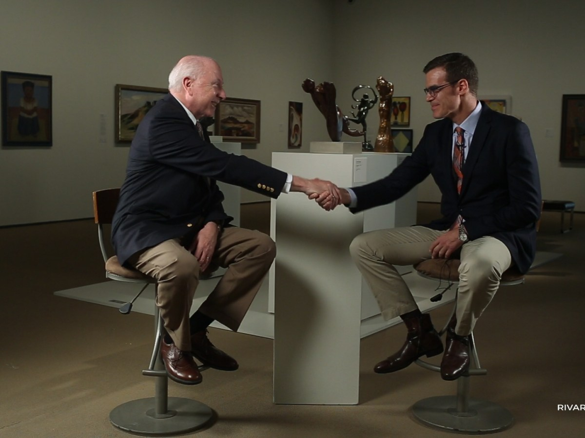 Outgoing McNay Art Museum Director William Chiego (left) shakes hands with incoming McNay Art Museum Director Richard Aste. Video still by Kathryn Boyd-Batstone and Scott Ball.