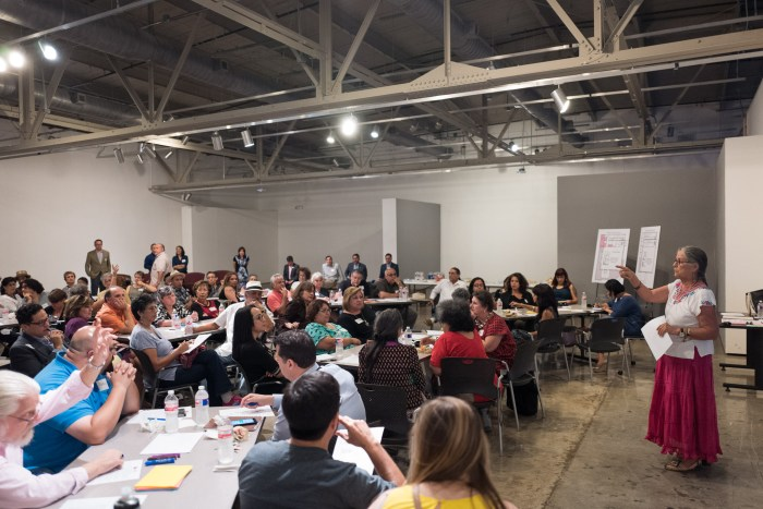 Community members raise their hands in response to a question from facilitator Linda Ximenes. Photo by Scott Ball.