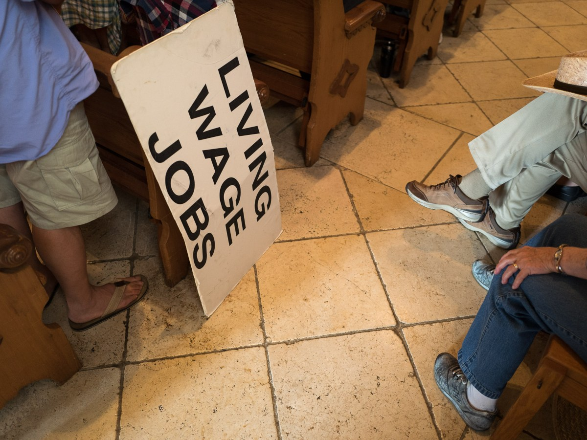 A sign advocating for higher wages rests alongside pew at San Fernando Cathedral. Photo by Scott Ball.