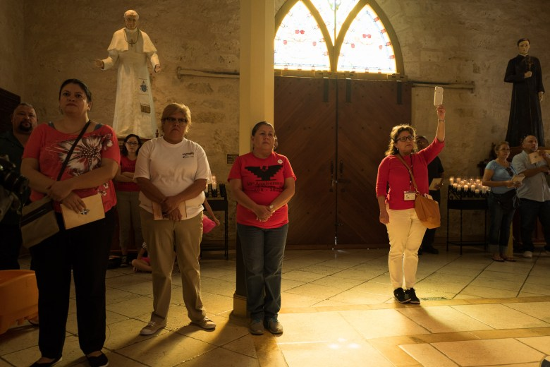 Teri Palos (right) holds up her iPhone as she records the service at San Fernando Cathedral. Photo by Scott Ball.