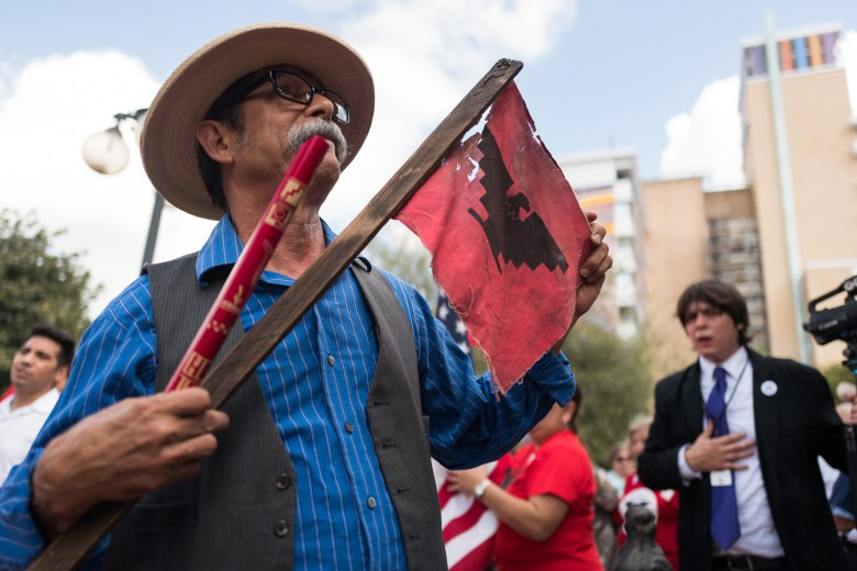 Eduardo Garza holds a flute and tattered United Farm Workers flag at Milam Park. Photo by Scott Ball.