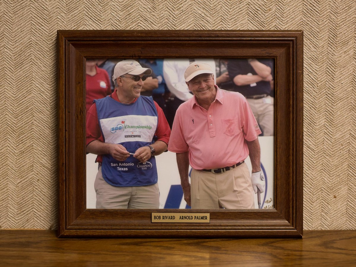 A framed photograph of the Director of the Rivard Report Robert Rivard (left) shares a moment with golf legend Arnold Palmer (right) as he caddies for him during the Champions Tour (framed photograph taken by Tom Reel, Express News). Photo by Scott Ball.