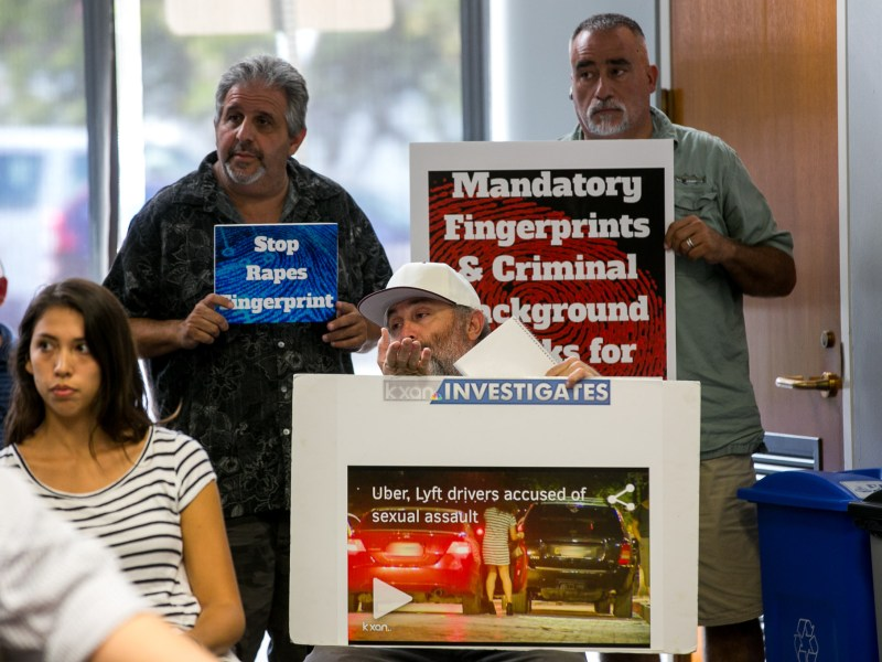 Taxi drivers hold up signs at a Transportation Advisory Board Council meeting. Photo by Kathryn Boyd-Batstone.
