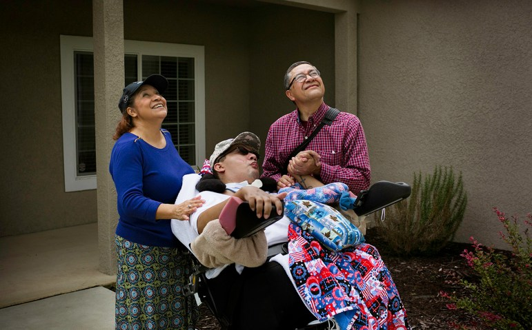 """After every walk, Julio Alvarado plays the song """"Proud to Be An American"""" while he and his son look up at the tall American flag in their front yard. Photo by Kathryn Boyd-Batstone."""