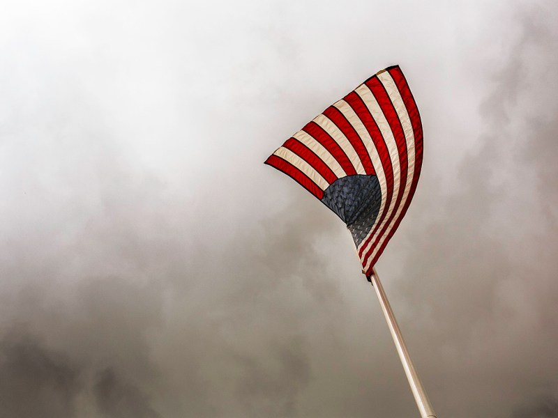 An American flag flies high in the sky in front of a residential home.
