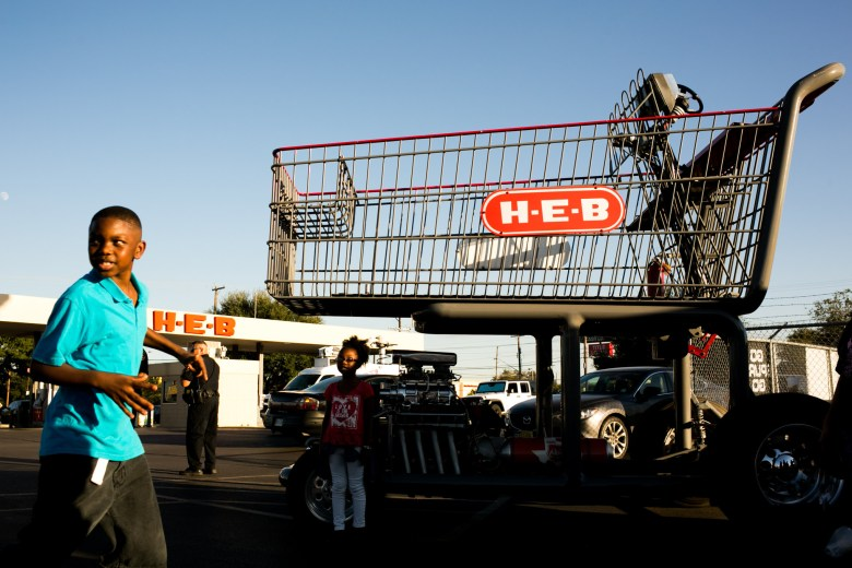Kids run by a large H-E-B cart marking the location of the celebration.