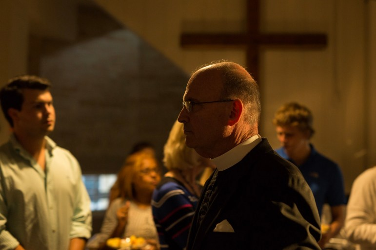 Christ Episcopal Church Rector Patrick Gahan walks through the crowd of attendees following a prayer.