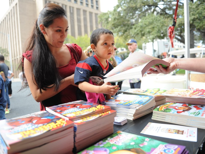 A mother and her son look through the books available at the 2013 Texas Book Festival at the Texas State Capitol in Austin.