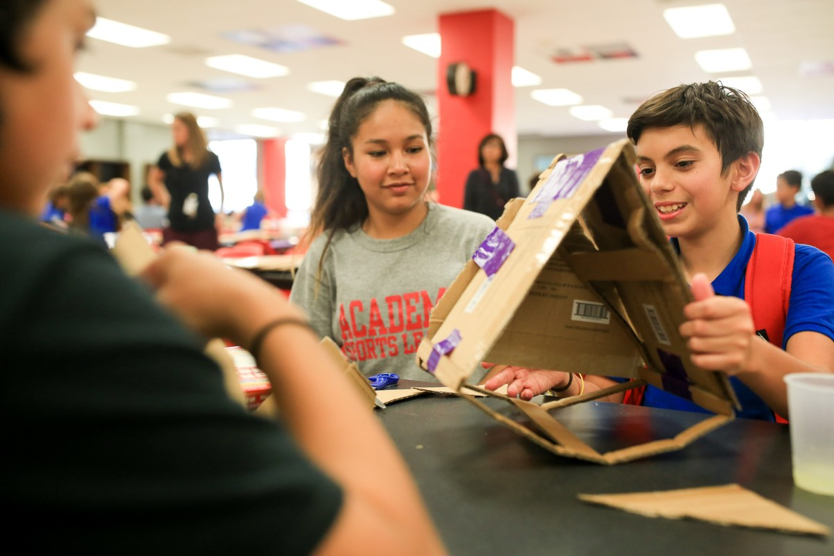 (From left)Brandon 12, Alexis 13, and Killian 13 work together while creating with cardboard and tape.