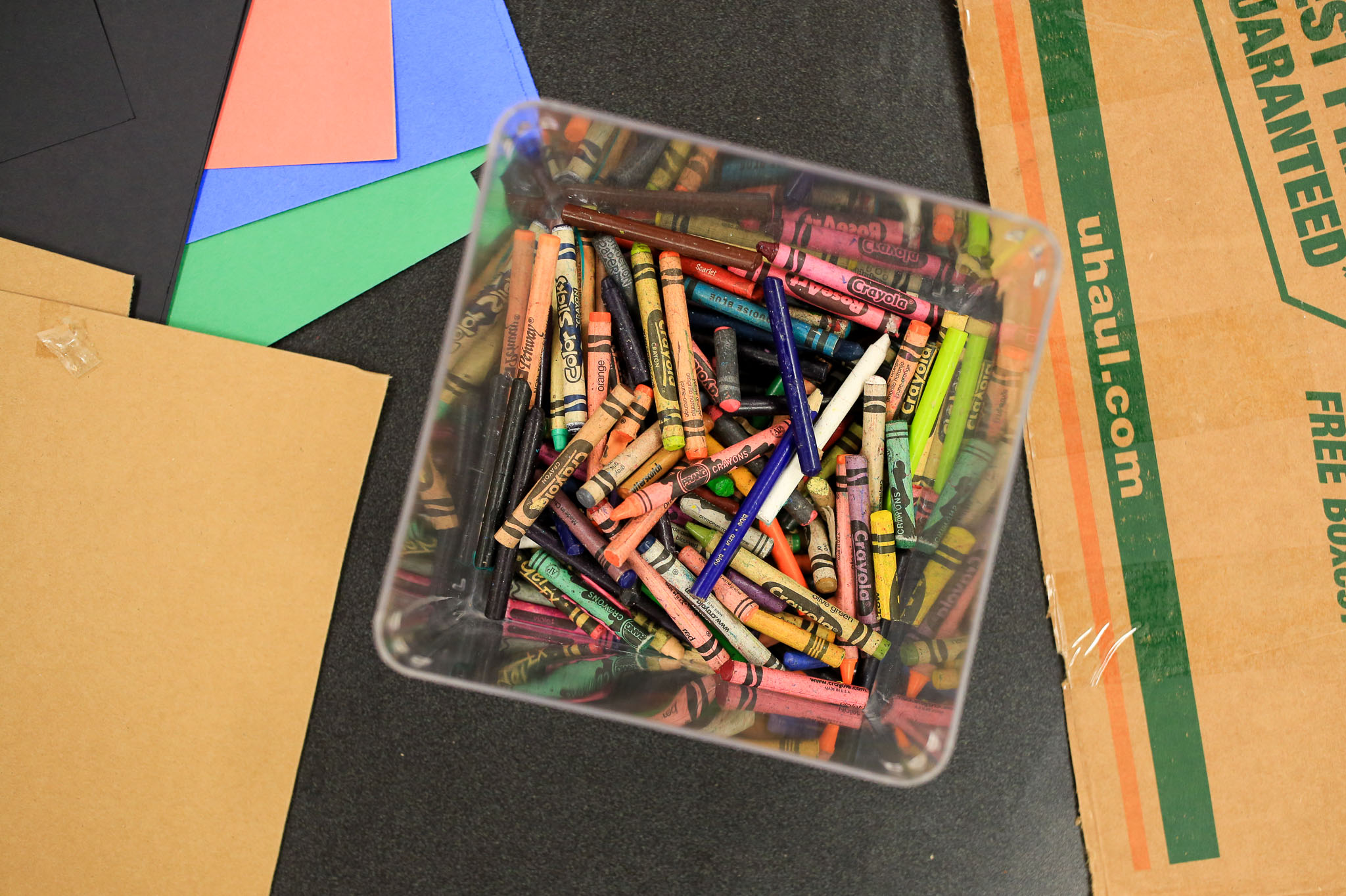 Craft paper, cardboard, and an assortment of Crayola crayons were laid out on tables for families to enjoy and create.