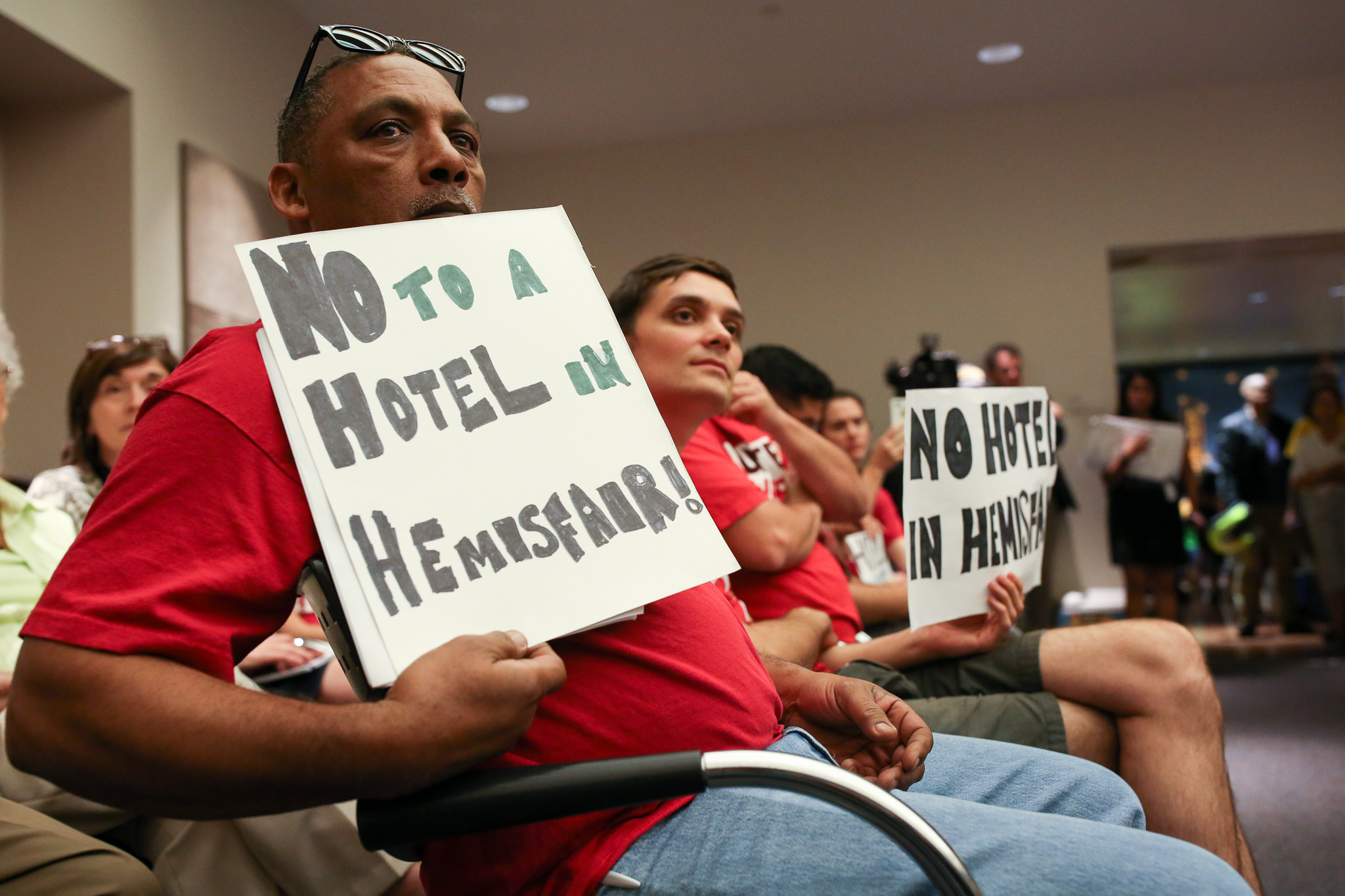 """Unite Here activist Rober Lee holds up a sign that reads: """"NO TO A HOTEL IN HEMISFAIR!"""""""