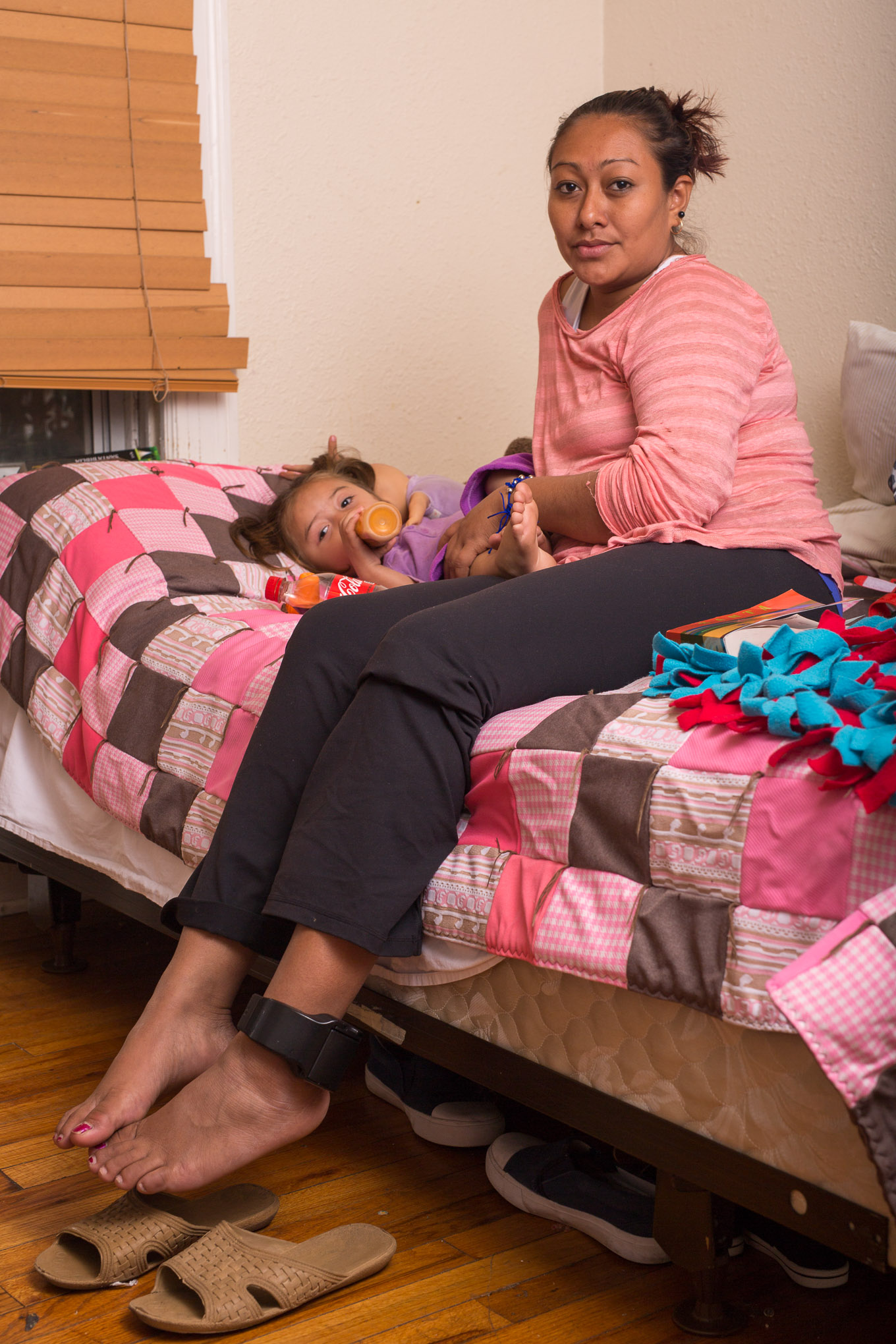 Odalma, 28, and her daughter Yanessa, 2, sit for a portrait on their temporary bed at Casa RAICES.