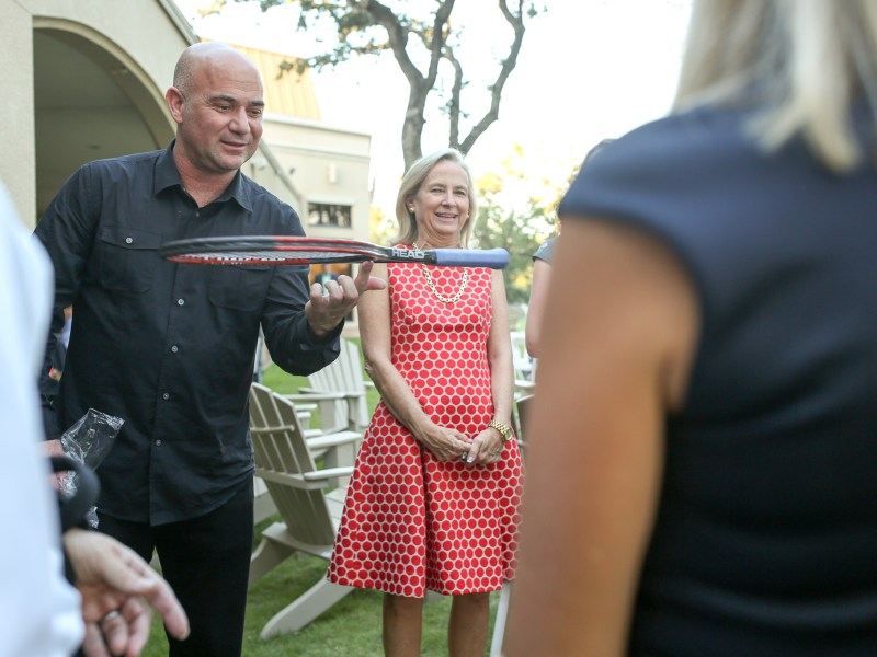Tennis champion Andre Agassi spins a tennis racket once used by him as attendees of a cocktail party surround him. Photo by Scott Ball.