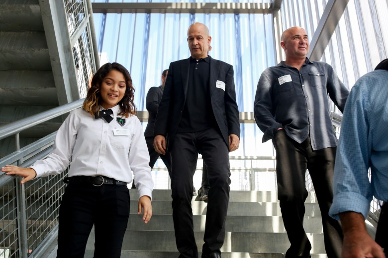 KIPP student ambassador Amanda, 15, leads Andre Agassi and Bobby Turner down a stairway during a tour of KIPP Cevallos campus. Photo by Scott Ball.