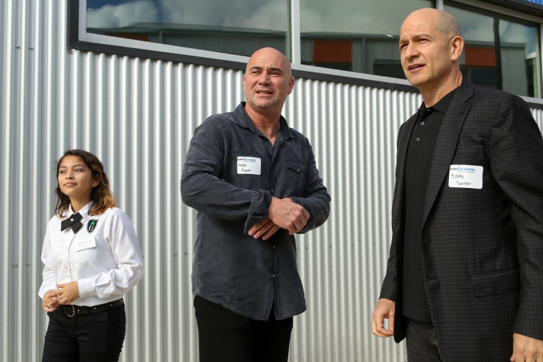 (left to right) KIPP student ambassador Amanda, 15, leads Andre Agassi and Bobby Turner through the KIPP Cevallos campus. Photo by Scott Ball.