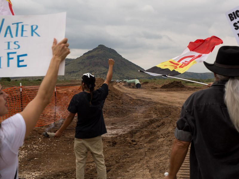 Protesters yell and wave flags and signs at pipeline workers.