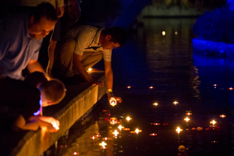 People place Diyas, or floating candles, in the San Antonio River.