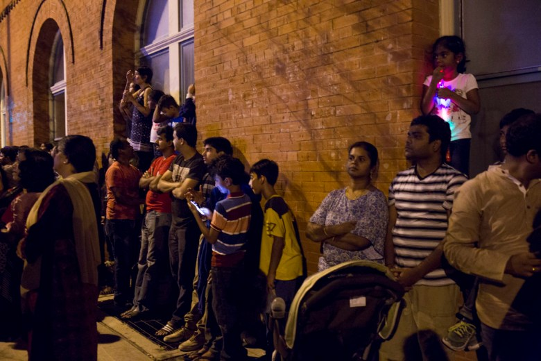 People line the street and climb up window sills in order to watch the Diwali Festival performances.