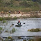 A kayaker and runners participate in the River Relay & Get Outdoors 5K.