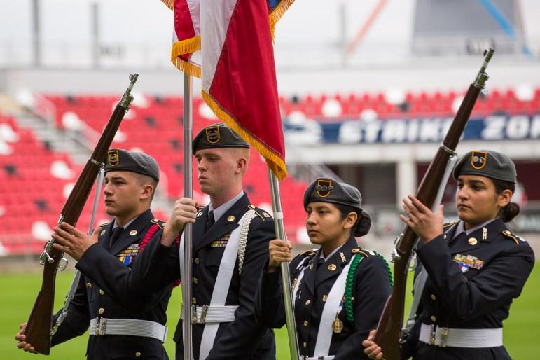 Roosevelt High School JROTC salute the flag.