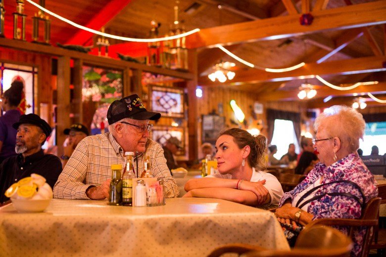 A veteran and his wife talk with an Acadiana Café waitress.