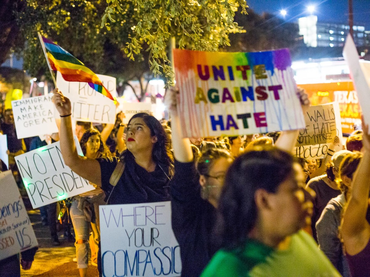 Haley Bayne carries a pride flag during the Anti-Trump protest.