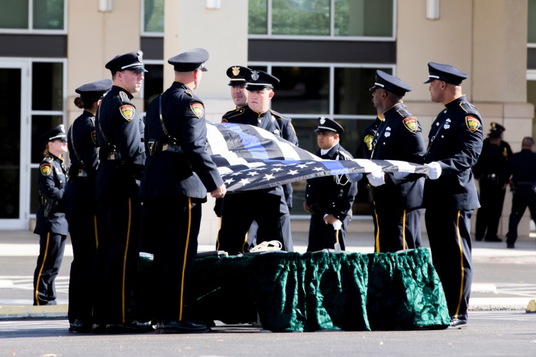 Honor Guard members practices the folding of the flag before Detective Marconi's casket is brought outside.