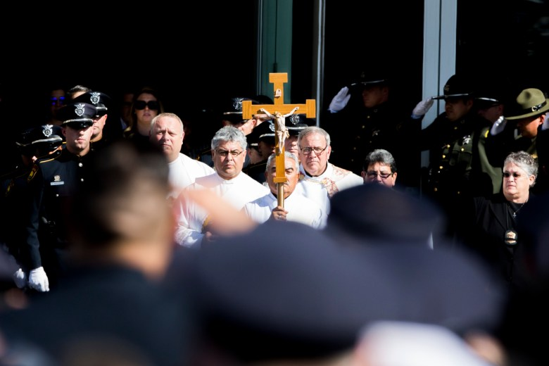 Detective Marconi's casket is carried out of the church after the funeral service.