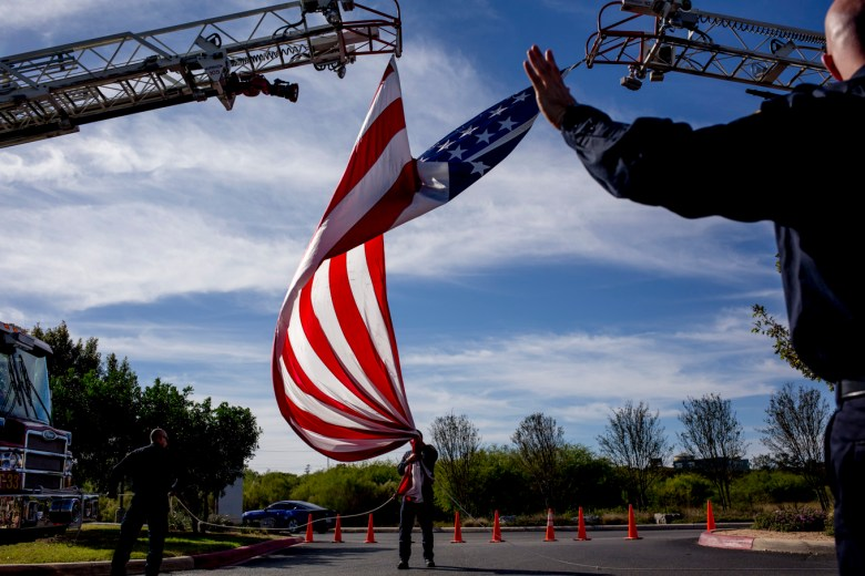 Firefighters fold up a 50 foot flag flown in Marconi's honor.