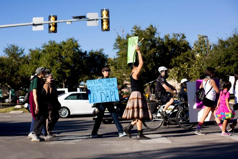Protestors walk along E Sonterra Blvd.
