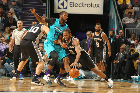 Kawhi Leonard #2 of the San Antonio Spurs handles the ball against Michael Kidd-Gilchrist #14 of the Charlotte Hornets during a game on November 23, 2016 at the Spectrum Center in Charlotte, North Carolina.