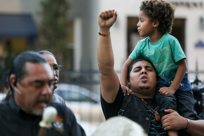 Ramon Vasquez holds up his fist and his son Ramon, 4, while singing a native song in front of Bank of America Plaza.