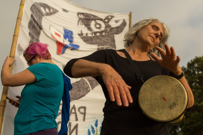 A protestors beats on a drum to the rhythm of a large group chant that can be heard from long distances.